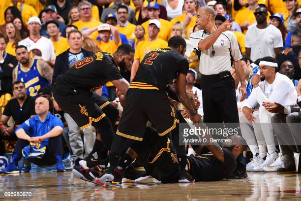 Tristan Thompson and Kyrie Irving help up LeBron James of the Cleveland Cavaliers during the game against the Golden State Warriors in Game Five of...