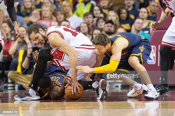 Tristan Thompson and Matthew Dellavedova of the Cleveland Cavaliers fight for a loose ball with Joakim Noah of the Chicago Bulls during the first...