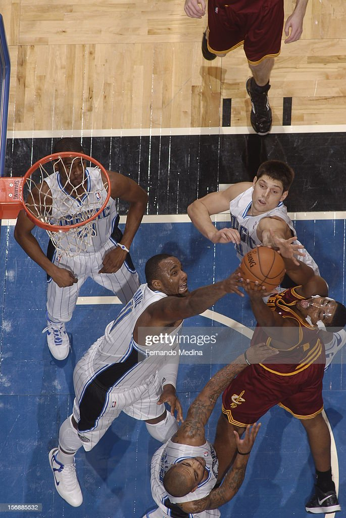Tristan Thompson #13 of the Cleveland Cavaliers grabs the ball against Glen Davis #11 and Nikola Vucevic #9 of the Orlando Magic on November 23, 2012 at Amway Center in Orlando, Florida.