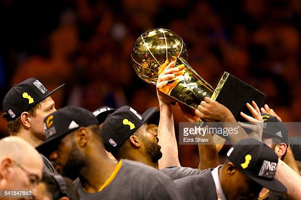 Tristan Thompson of the Cleveland Cavaliers holds the Larry O'Brien Championship Trophy after defeating the Golden State Warriors 9389 in Game 7 of...
