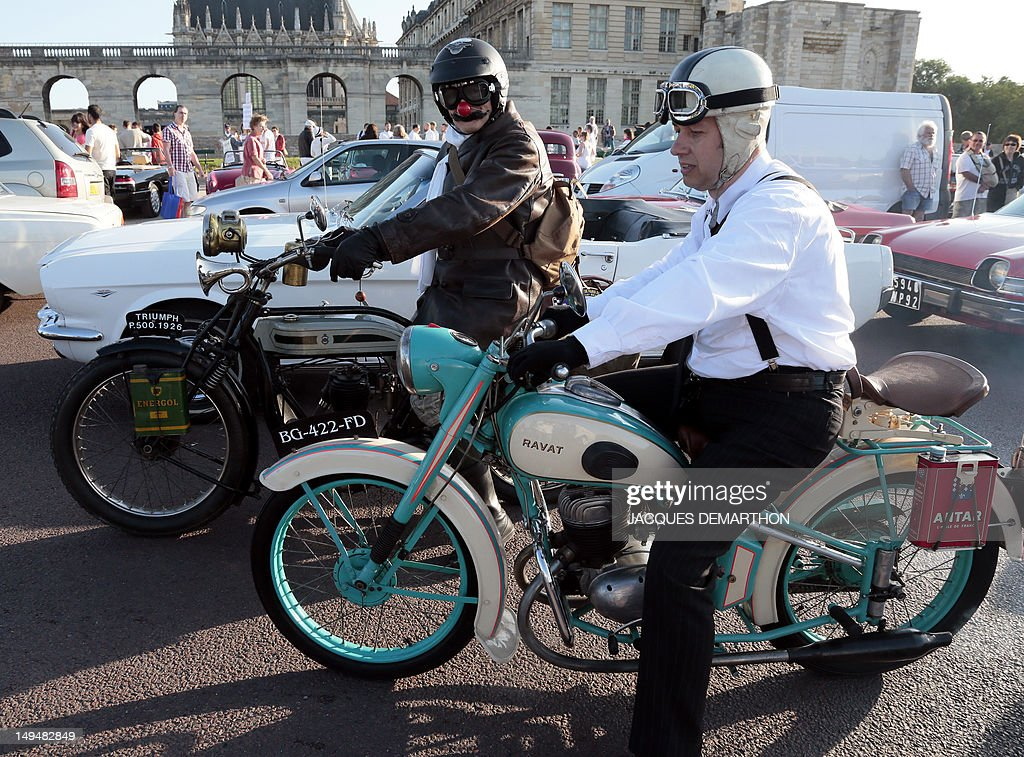 A Triumph (L) and a Ravat (R) motorcycles pass by the Chateau de Vincennes, outside Paris, on July 29, 2012, during a vintage cars parade as part of the fifth summer edition of the 'Traversee de Paris Estivale' ('Summer Paris Crossing'), the largest gathering of classic vehicles in the French capital streets. AFP PHOTO / JACQUES DEMARTHON
