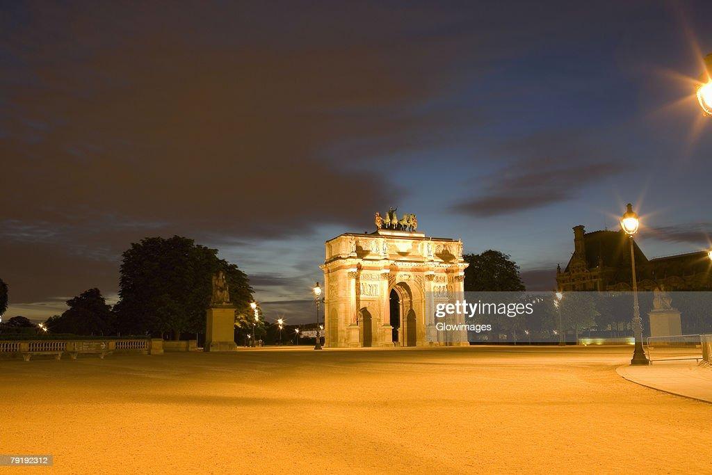 Triumphal arch lit up at night, Jardin De Tuileries, Paris, France : Foto de stock