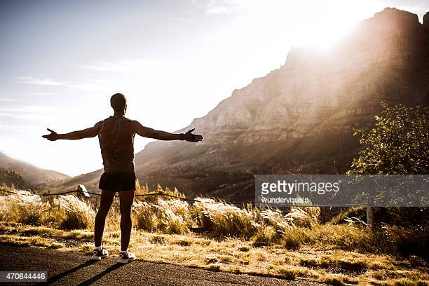 Triumphant African American athlete enjoying fitness in nature