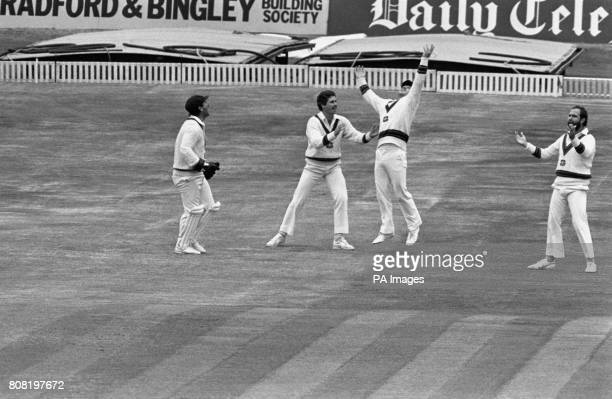 A triumphant Australian fielder Allan Border leaps into the air after a superb catch also joining in the celebration wicketkeeper Rod Marsh Graeme...