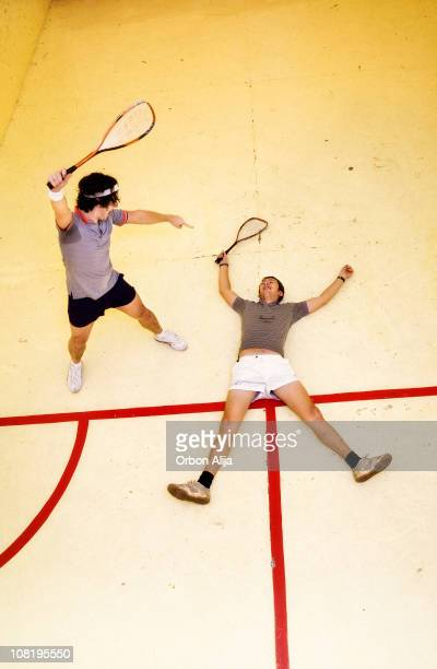 Triumphant Man Pointing at Squash Player Lying on Court