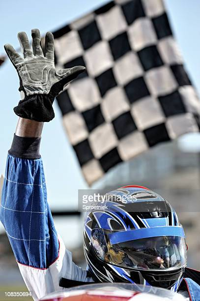 Triumphant racing driver waves at crowd