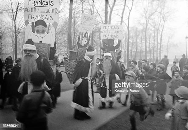 Trois hommessandwichs déguisés en Père Noël se promenant dans la rue et portant un écriteau où l'on recommande aux mamans françaises d'acheter des...