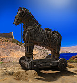 3D render of Homer's Trojan Horse in front of the Walls of Troy and the Aegean Sea.