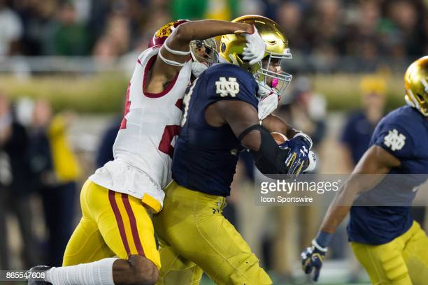 Trojans cornerback Isaiah Langley tries to bring down Notre Dame Fighting Irish running back Josh Adams during the college football game between the...
