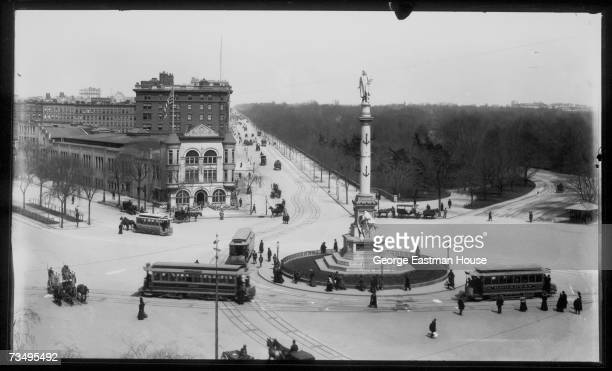 Trolley cars pedestrians and a horsedrawn carriages negotiate the traffic around the monument to Chistopher Columbus at the southwestern corner of...