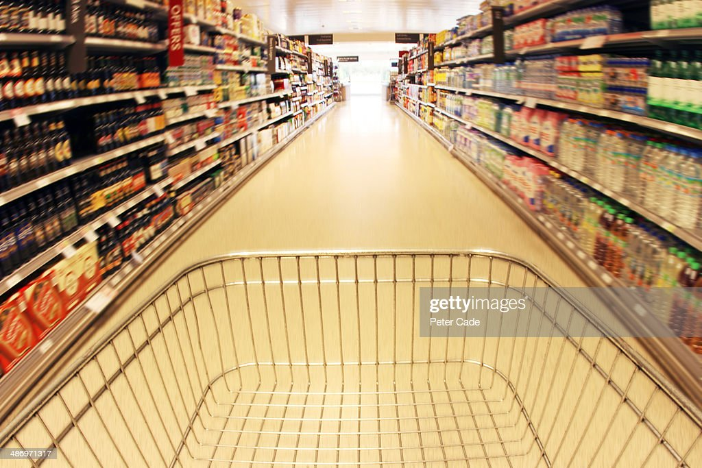 Trolley in supermarket aisle : Stock Photo