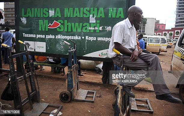 Trolley pushers wait for customers at a bus stop near an advertisement for a new mobile telephonebased banking initiative called MShwari in the...