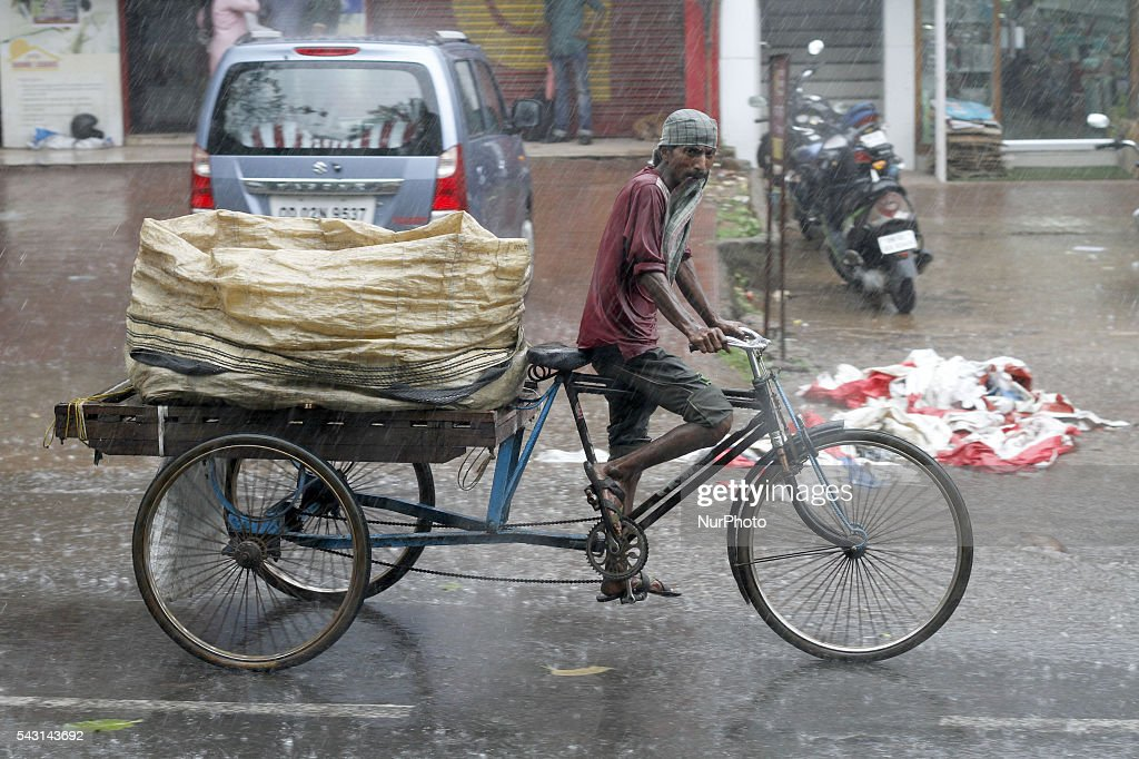 A trolley rickshaw puller paddles his trolley wade through in the monsoon rain in the eastern Indian city Bhubaneswar, India, Sunday, 26 June 2016.