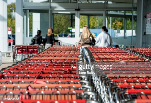 Trolleys and shoppers outside a supermarket : Stock Photo