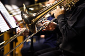 Trombones in the hands of musicians in the orchestra closeup in dark tones
