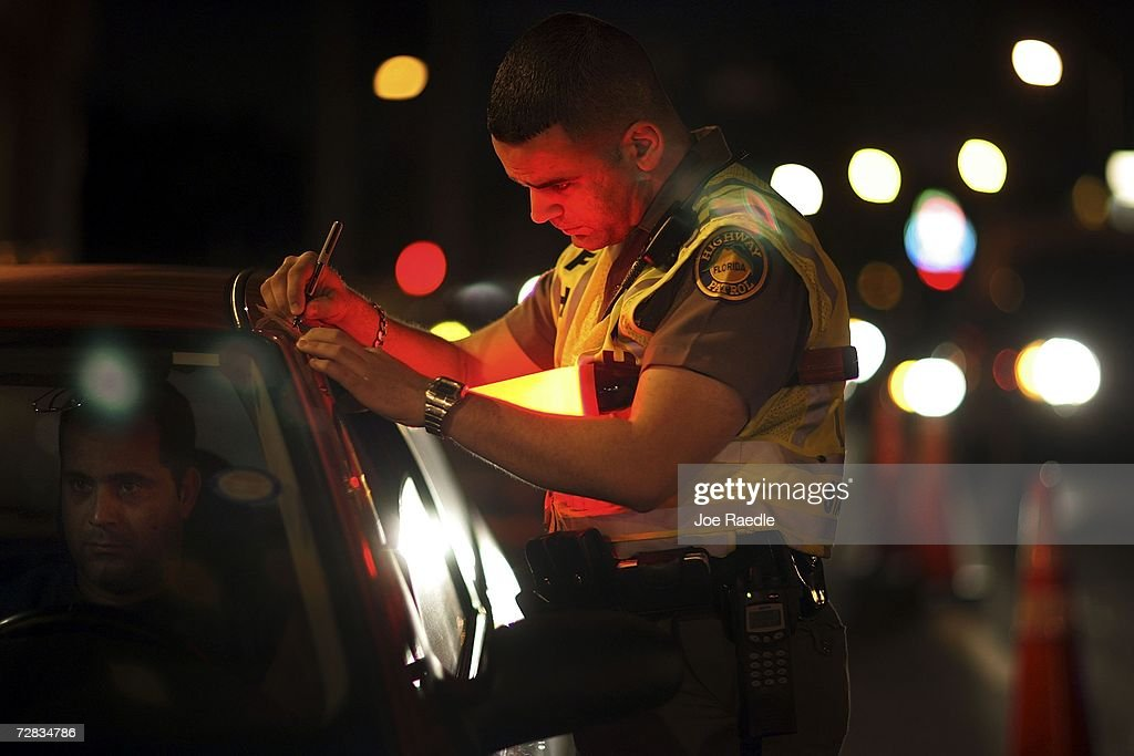 Trooper David Casillas, from the Florida Highway Patrol, talks to a driver at a DUI checkpoint December 15, 2006 in Miami, Florida. The city of Miami, with the help of other police departments, will be conducting saturation patrols and setting up checkpoints during the holiday period looking to apprehend drivers for impaired driving and other traffic violations.