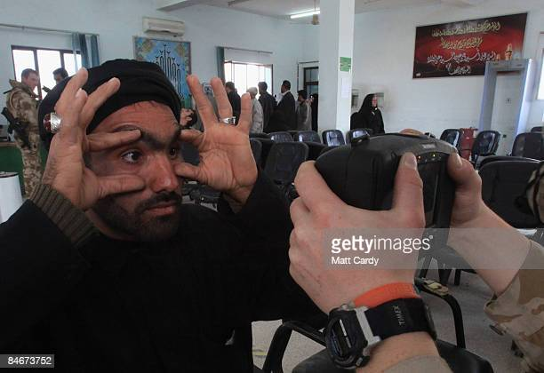 Trooper of the Queen's Royal Hussars uses a iris recognition camera to photograph a man's eyes as he crosses from Iran into Iraq at the Shalamcheh...