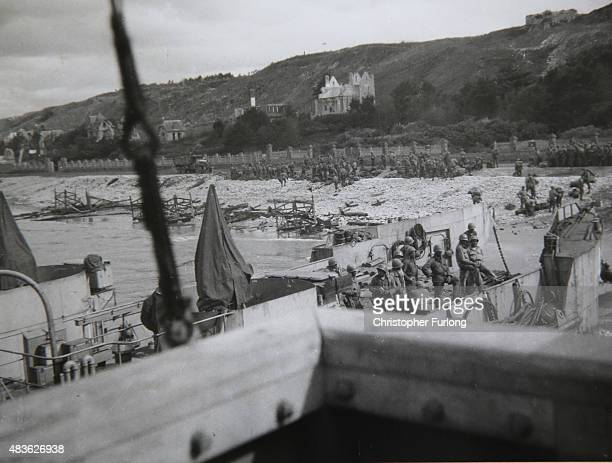FEATURE** Troops and equipment land on the Normandy beaches in this photograph taken by WWII veteran Brian Carter from the bridge of the landing...