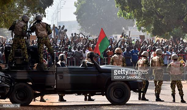 Troops face protestors on October 30 2014 in Ouagadougou Hundreds of angry demonstrators in Burkina Faso stormed parliament before setting it on fire...