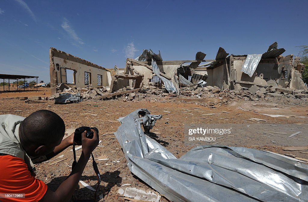 Troops from Niger and Mali on January 29, 2013 entered the town of Ansongo which along with Gao was recaptured by French-led soldiers over the weekend in a lightning offensive against radicals holding Mali's north. A man films a building destroyed by French aerial bombing.