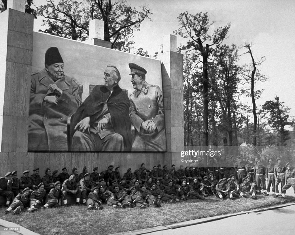 Troops from the British Victory Parade in Berlin rest under the picture of the 'Big Three' - Churchill, Roosevelt and Stalin.
