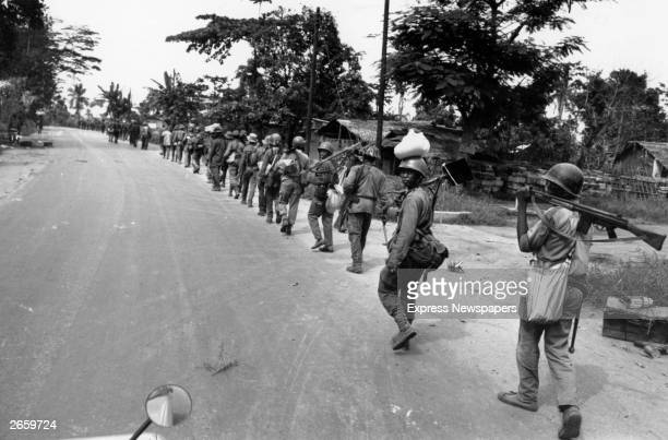 Troops from the Nigerian Federal Army marching along a road after routing Biafran troops at Port Harcourt during the Biafran War