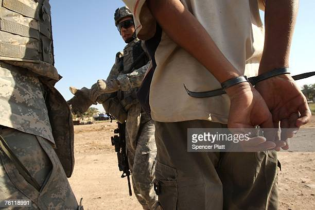 Troops from US Army Delta Company 212 Cavalry detain a boy suspected of planting an IED in the Ghazaliya neighborhood which has been used as a base...