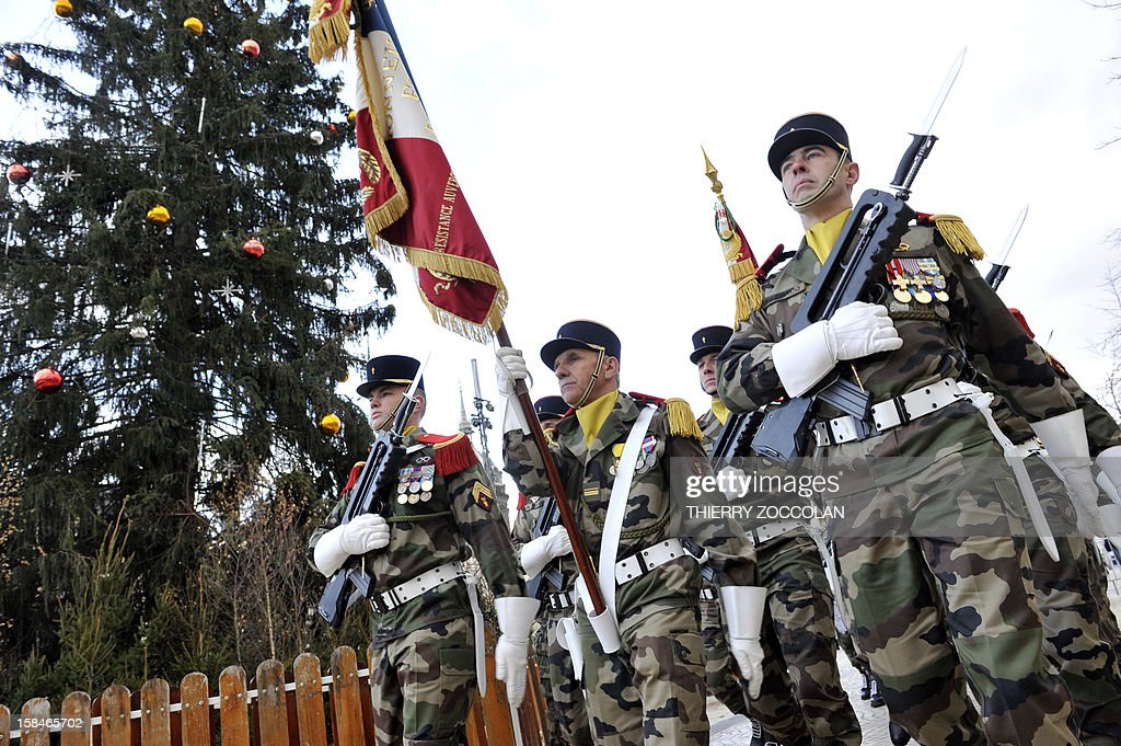 Troops of the 2nd Engineer French Foreign Legion Regiment parade with their flag, on December 17, 2012 in Clermont-Ferrand, central France, during a ceremony marking the dissolution of a joint tactical bataillon that served in Afghanistan from May to November 2012. France joined the NATO coalition in late 2001 to help prop up the new government against an insurgency, which began after a US-led invasion toppled the Taliban government earlier that year for giving refuge to Osama bin Laden and his Al-Qaeda network, following the 9/11 attacks on New York and Washington. ZOCCOLAN