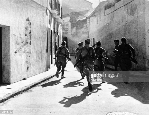 Troops of the Foreign Legion run through the streets of Merida during the Spanish Civil War with their rifles at the ready