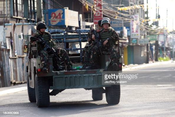 Troops on board a military vehicle patrol along the streets of southern Philippine city of Zamboanga as they rescued residents held hostage by Muslim...