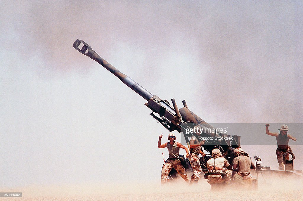 Troops on ground firing M198 Howitzer gun