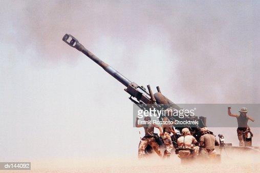 Troops on ground firing M198 Howitzer gun