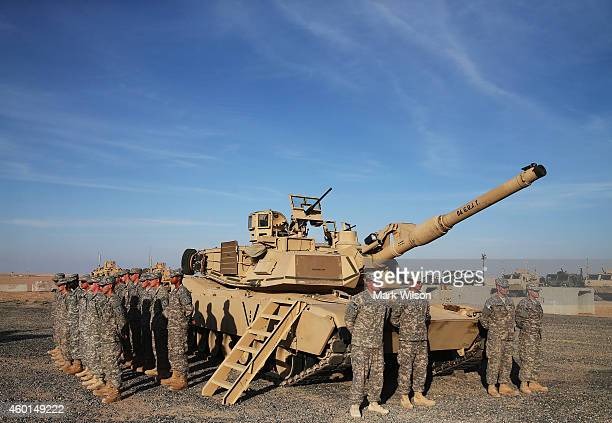 S troops stand at attention next to a Abrams tank waiting for the arrival of Secretary of Defense Chuck Hagel December 8 2014 at Camp Buehring Kuwait...