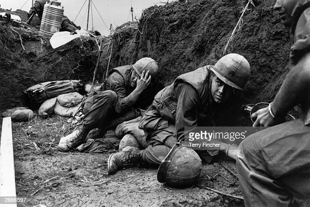 US troops take cover from the Vietcong in a trench on Hill Timothy during the Vietnam War