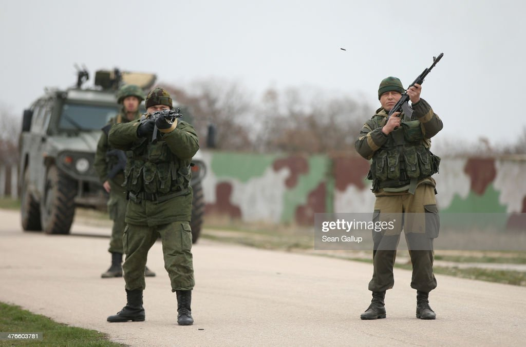 Troops under Russian command fire weapons into the air and scream orders to turn back at an approaching group of over 100 hundred unarmed Ukrainian troops at the Belbek airbase, which the Russian troops are occcupying, in Crimea on March 4, 2014 in Lubimovka, Ukraine. The Ukrainians are stationed at their garrison nearby, and after spending a tense night anticipating a Russian attack following the expiration of a Russian deadline to surrender, in which family members of troops spent the night at the garrison gate in support of the soldiers, their commander Colonel Yuli Mamchor announced his bold plan this morning to retake the airfield by confronting the Russian-lead soldiers unarmed. The Russian-lead troops fired their weapons into the air but then granted Mamchor the beginning of negotiations with their commander. Russian-lead troops have blockaded a number of Ukrainian military bases across Crimea.