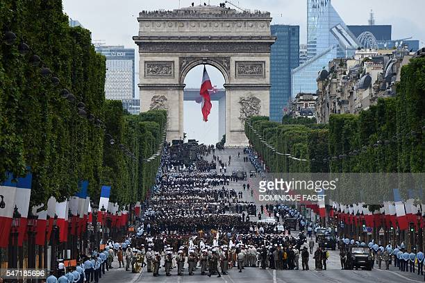 TOPSHOT Troops wait near the Arc de Triomphe in Paris before taking part in the annual Bastille Day military parade on the ChampsElysees avenue on...