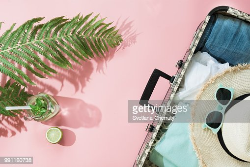 Tropacal summer vacation. Straw beach sunhat, sun glasses, beach towel leaf of fern with shadow on pastel pink background. Top view with copy space. Summer. : Foto de stock