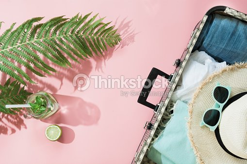 Tropacal summer vacation. Straw beach sunhat, sun glasses, beach towel leaf of fern with shadow on pastel pink background. Top view with copy space. Summer. : Stock Photo