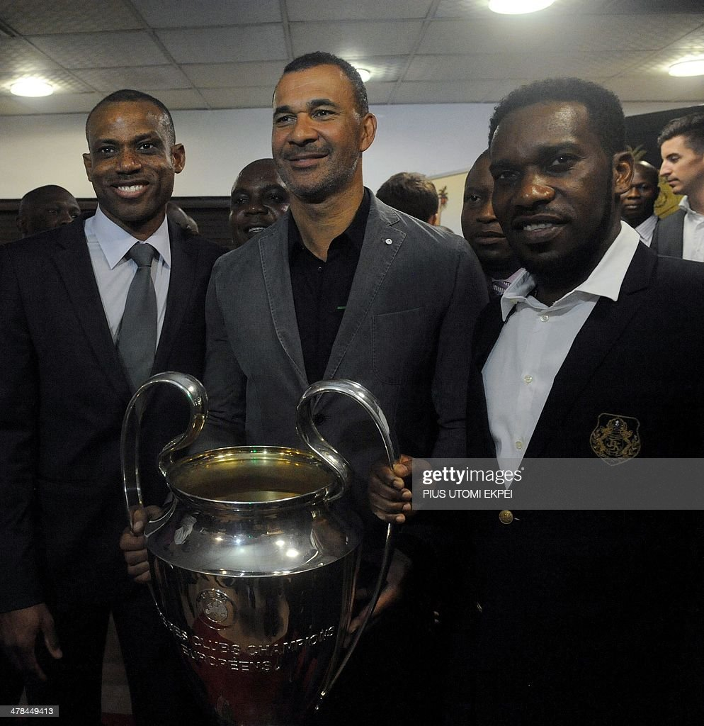 Trophy Tour Ambassador Ruud Gullit (C) holds the trophy, flanked by former Nigerian footballers Sunday Oliseh (L) and J. J. Okocha during a visit to the governor with the UEFA trophy in Lagos on March 13, 2014. Ruud Gullit is in Nigeria to begin a three-nation UEFA Trophy tour. AFP PHOTO / PIUS UTOMI EKPEI