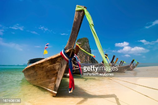 Tropical beach landscape. Thai long tail boats at ocean coast : Stockfoto