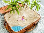 tropical beach scene inside a suitcase aerial view