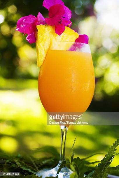 A tropical cocktail garnished with fruit in an outdoor setting.