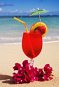 A tropical cocktail on the beach garnished with fruit and flowers.