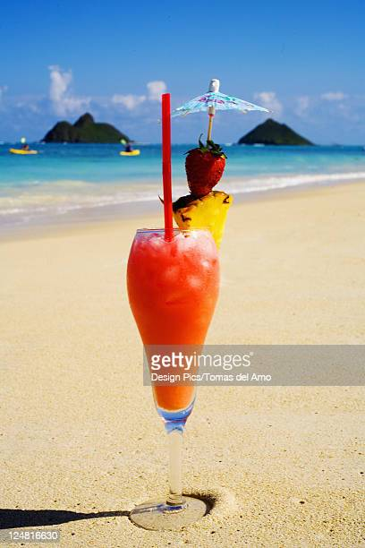 A tropical cocktail on the beach, Mokulua Islands and kayakers in background.