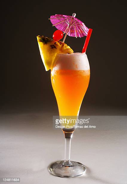 A tropical drink garnished with fruit.