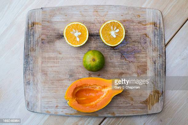 Tropical fruit face on wooden cutting board