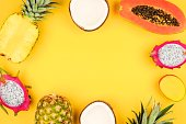 Tropical fruit frame with pineapple, dragon fruit, papaya, coconut and mango on a bright yellow background