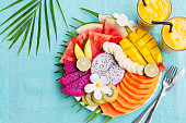 Tropical fruits assortment on a white plate with palm tree leaf with mango smoothie, textile blue background. Top view. Copy space