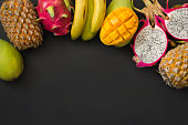 Tropical fruits pineapple, banana, dragon fruit and mango on black background. Top view. Copy space.