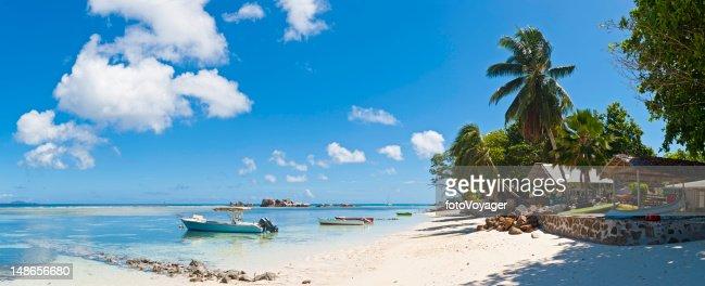 Tropical island beach house boats idyllic palm tree lagoon Seychelles : Stock Photo